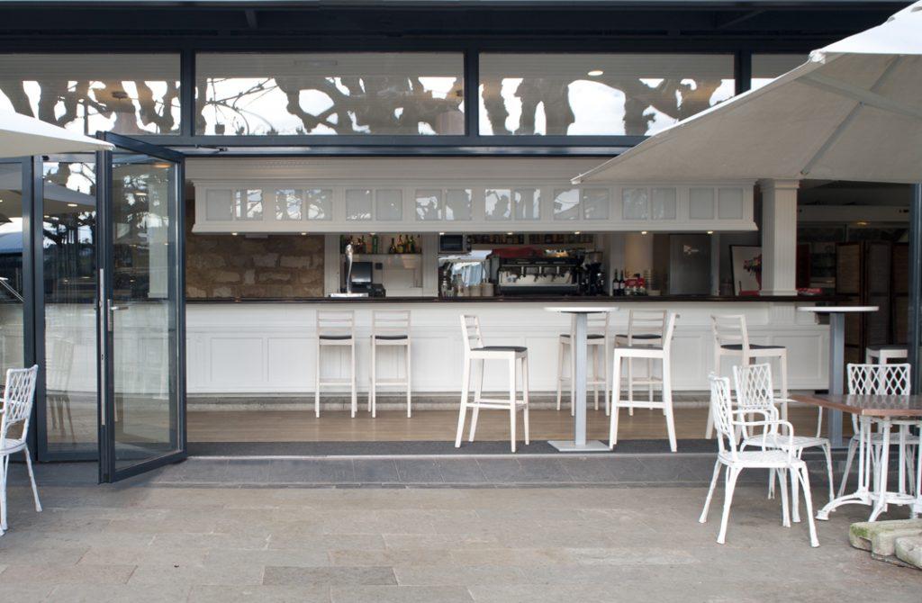 Interior cafeteria con diseño cerramiento de cristal a terraza que se puede abrir completamente, en Club Jolaseta de Neguri - Getxo (Bizkaia)