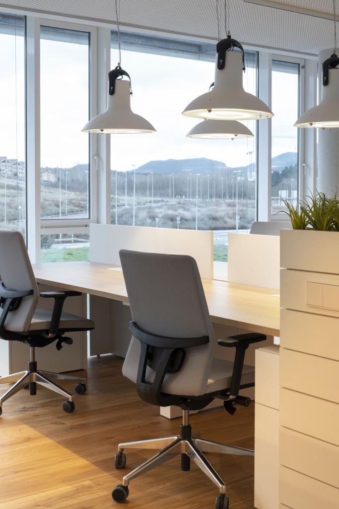 Diseño de oficina con puestos de trabajo en blanco separados por muebles bajos